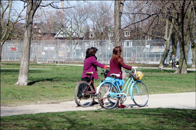 two-ladies-pushing-bikes