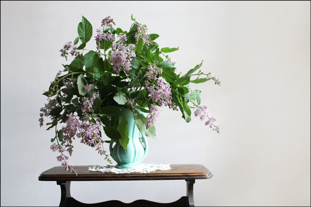 green vase with lilacs