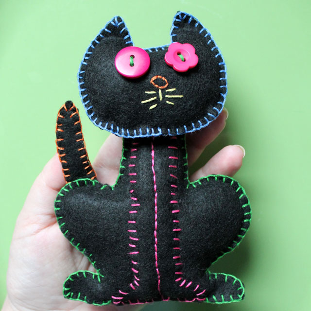 embroidered felt cat decoration with hand for scale