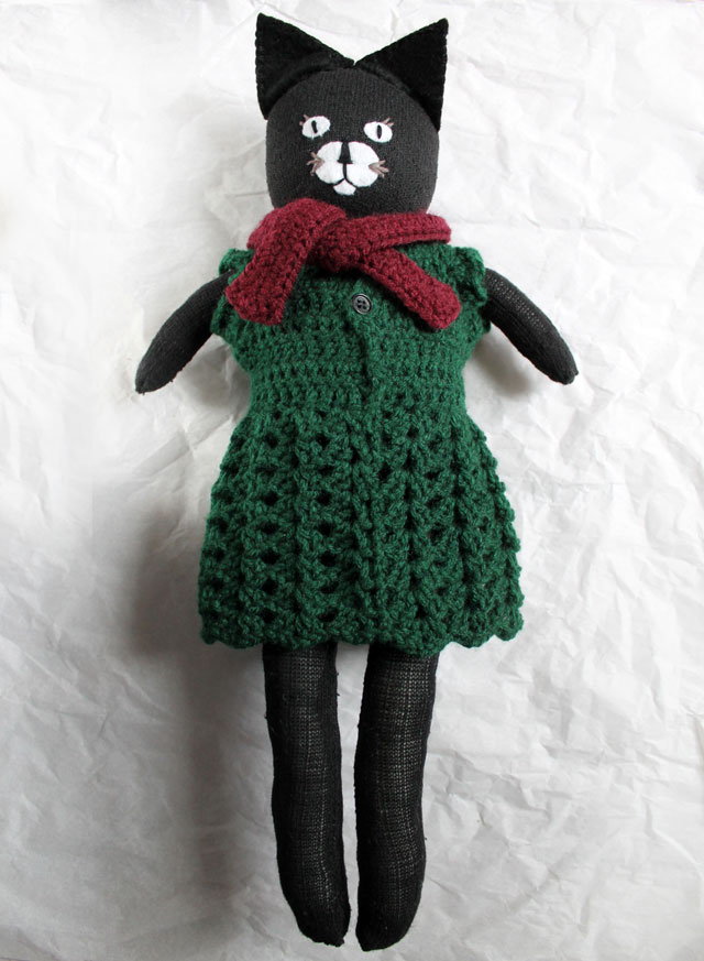 handmade doll wearing crocheted dress and scarf