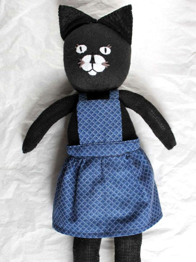 handmade sock doll wearing bibbed skirt