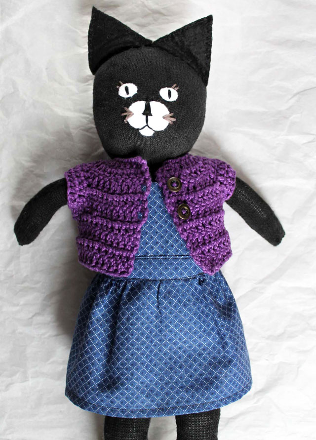 handmade toy cat wearing crocheted sweater and bibbed skirt