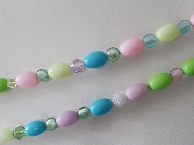 close up of handmade easter decoration garland with beads and eggs