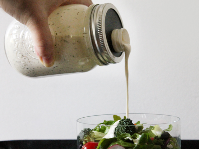 pouring salad dressing from diy mason jar container with spout
