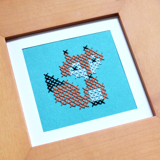 close up cross stitched fox on paper
