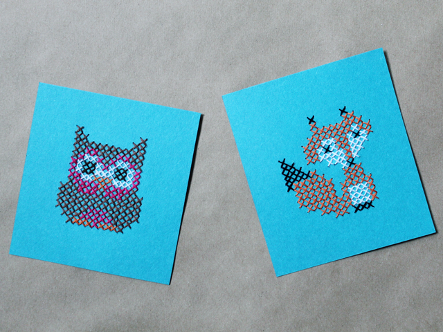 simple patterns cross stitched onto paper fox and owl