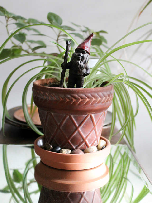 cast iron gnome in a house plant