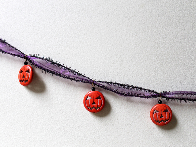 easy halloween decoration garland using pumpkin beads and ribbon from michaels