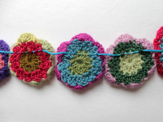 sewing crocheted flowers to make garland