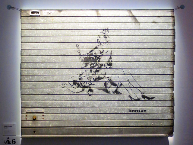 bansky screen print graffiti on metal door displayed in toronto exhition