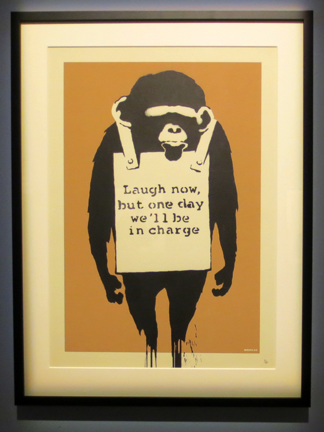 laugh now monkey banksy print on display in toronto