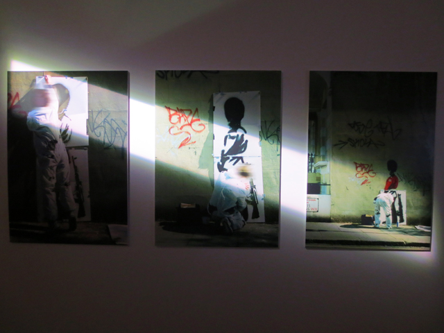 photographs by steve lazerides of banksy while he created a piece of stencilled graffiti