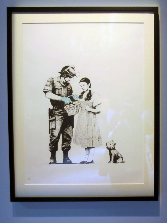 stop and search print by banksy dorothy and toto and policeman on display in toronto