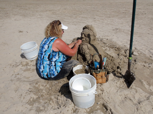 lady making sand sculpture on beach