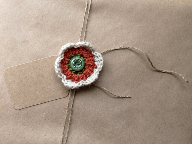 alternative christmas gift wrapping brown papper with hand crocheted flower and repurposed button gift topper