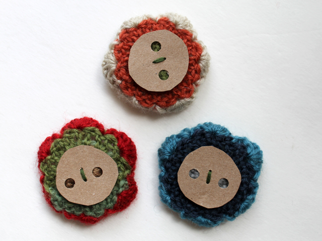 back of crocheted flower gift topper decorations finished with a piece of cardboard for attaching