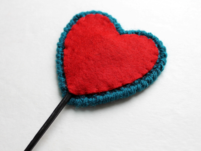 heart shaped plastic canvas used to make a pick for a vase or plant back side completed with felt