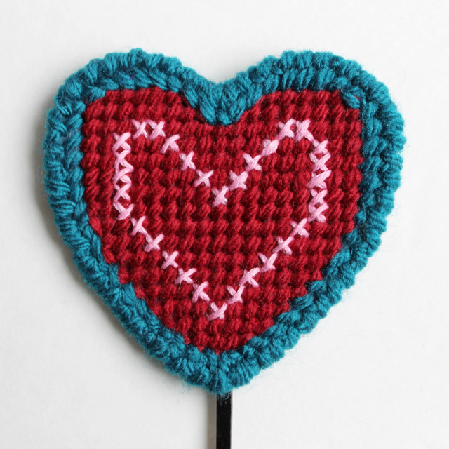 needle point plastic canvas heart finished with a cross stitched heart