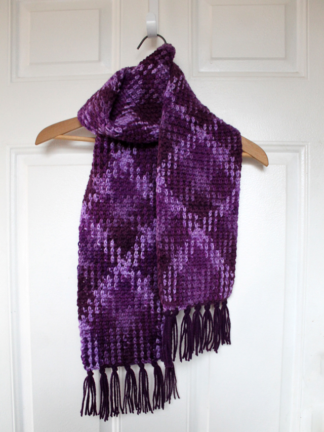 crocheted scarf loops and threads pooling yarn purple plush colourway with added fringe