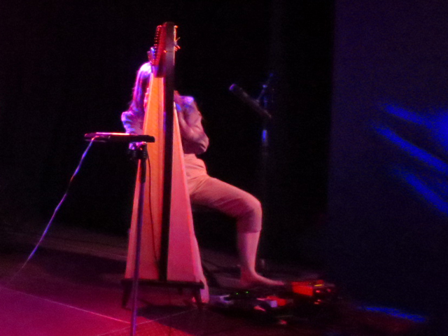 emilie kahn in action singing into base of harp controling effects pedals with her feet