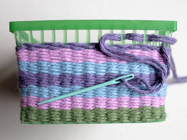 weaving yarn through old berry basket to make an easter basket