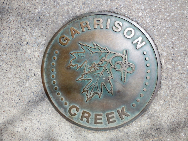garrison creek sign on sidewalk king street west toronto
